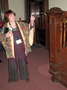 Kitty explaining stairs in the Chapel. Note Roycroft symbol on post.