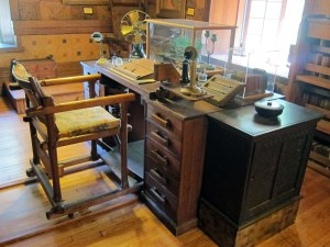 His desk with chair on rails for easy movement in and out