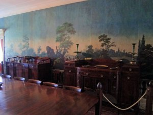 Part of the original French wallpaper in the central entranceway. Table reproduces the original