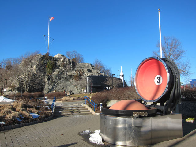 Looking from the entrance to Sub Base New London - flag on hill. Open hatch in foreground is the top of a Polaris Missile Tube.